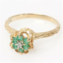 Edwardian 10K Yellow Gold High Set Emerald and Diamond Ring: An Edwardian 10K yellow gold ring featuring a diamond and emerald flower mounted in a high setting with an etched shank.