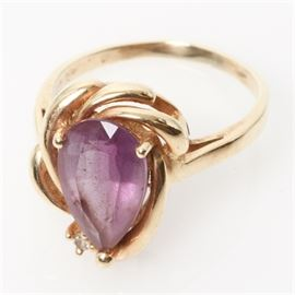 14K Yellow Gold, Pear Cut Amethyst, and Diamond Cocktail Ring: A 14K yellow gold ring featuring one center pear cut amethyst in a spiraled gold frame, accented by one round brilliant cut diamond.