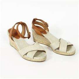 Coach Sandals: A pair of Coach sandals. These designer sandals feature a woven wedge design with a crossed toe-box and adjustable leather ankle straps,. The Coach trademark label is displayed to the insole lining; additional branding appears on the soles. These shoes are a size 6.5.