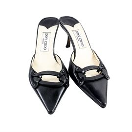 Jimmy Choo Black Leather Mules: A pair of Jimmy Choo mules in size 37.5. This high-end designer style features a black leather upper with a pointed toe, a pierced oval accent, a beige leather insole with a Jimmy Choo label, a brand stamped leather sole and a narrow heel.