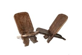 Pair of African Birthing Chairs: A pair of African birthing chairs. This hand rendered pair has been constructed from solid mahogany, with carved designs of a crocodile on one, and a warrior mask on the other. Each chair consists of two pieces of wood that simply pull-apart for storing. The use of these chairs dates from antiquity and are still in use today.
