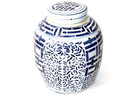 Chinoiserie Blue and White Ceramic Ginger Jar: A chinoiserie style blue and white ceramic ginger jar. The jar is in a tapered form with flat fitted lid, geometric design to the lid, jar's shoulder and front and back. The jar has an overall foliate pattern and has protective felt to the base.