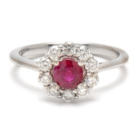 14K White Gold Ruby and Diamond Ring: A 14K white gold ruby and diamond halo ring comprising a center round cut heat treated ruby gemstone framed with a halo of round brilliant cut diamonds estimated at 0.45 ctw with a bright polish finish.