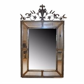 Metal framed Mirror: A metal framed mirror. This mirror is rectangular in shape with an outer mirrored border presented in a gold and silver tone metal frame. The top of the mirror features a scrolling foliate motif with a central urn design. The back of this mirror has a wire of the back for hanging.