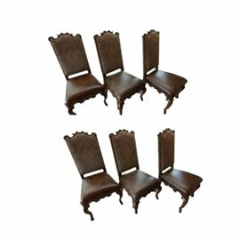 Six Leather and Embroidery Dining Chairs: A group of six dining chairs with embroidered and leather upholstery. Each of these chairs features a curved and shaped crest over a long back, embroidered in brown fabric. Each seat is upholstered in a treated leather, leading to a shaped seat rail and four cabriole style legs with hoof feet.
