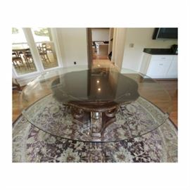 """Louis XV Style Round Pedestal Dining Table: A Louis XV style round pedestal dining table. This table features a round glass top surface over a round wood surface with scalloped edging and carving to the perimeter. The table rises on four """"S"""" scrolls with carving that are attached to a molded edge base."""