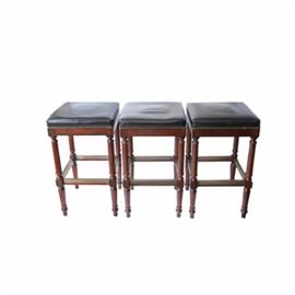 Three Wooden and Leather Bar Stools: A collection of three wooden and leather bar stools. Each stool features a square black leather seat with nailhead trim over above apron sides, resting on turned ring and stick legs ending in peg feet. The stools each include stretchers for support.