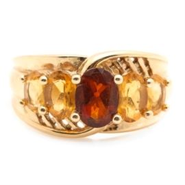 14K Yellow Gold Garnet and Citrine Ring: A 14K yellow gold garnet and citrine ring. This ring features a center prong set oval garnet stone flanked by prong set citrine stones and accented with pierced lattice detail.