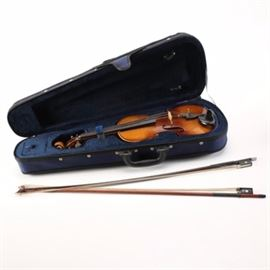 Kiso Suzuki Violin: A Kiso Suzuki violin. This violin features wooden tuning pegs and a black chin rest with a label to the inside which indicates manufacture in 1969. The violin is presented in a blue carrying case with two bows.