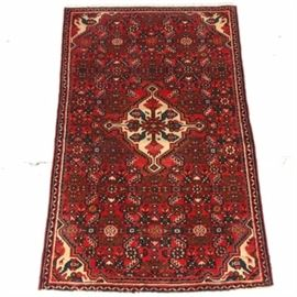Hand-Knotted Northwest Persian Area Rug: A Northwest Persian area rug. This rectilinear wool rug, possibly from Hamadan, is hand-knotted in a palette of madder red, cream, and teal. It begins with a central star medallion in cream over an abrashed red field. The medallion features stylized depictions of palmettes, in teal, rose, pink, and green, as well as arrow pendants in four directions. The field features a stylized herati pattern with kaleidoscopically arranged palmettes, oak leaves, flowers, and vines, cornered by shallow spandrels in cream, the spandrels each including a tiny depiction of a four-legged animal. Framing the field are narrow compound borders including a sawtooth pattern, stripes in red, cream, and black, and a running water guard border. Selvedges are overcast, the rug finishing at either end with short cotton warp fringe. It is unlabeled.
