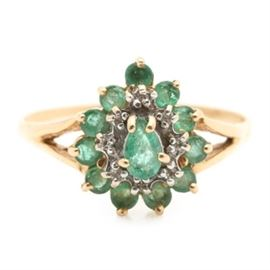 14K Yellow Gold Emerald and Diamond Ring: A 14K yellow gold emerald and diamond ring. This ring features a pear shaped setting housing a center prong set emerald encircled by an inner ring of diamond and an outer ring of emeralds flanked by split shoulders affixed to a slender shank.
