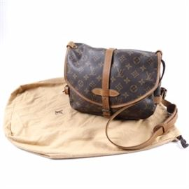 Vintage Louis Vuitton Saumer Handbag: A vintage Louis Vuitton Saumer handbag. This brown monogram coated canvas handbag features brown leather accents with brass hardware. Other This saddle bag design has adjustable straps including a leather shoulder strap, a flap and buckle closure, and a brown cloth interior with multiple compartments. The interior has a leather tab with date code AR0911 and is made in France. Dust bag included.