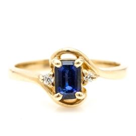 14K Yellow Gold Sapphire and Diamond Ring: A 14K yellow gold sapphire and diamond ring. A prong set emerald cut blue sapphire is flanked by two diamonds in an open criss cross setting.