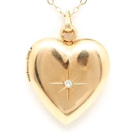 14K Yellow Gold Diamond Heart Locket: A 14K yellow gold diamond heart locket. A single cut diamond is set in the center of this heart locket that has engraving in the shape of a star. The locket hangs from a curb chain that closes with a lobster clasp.