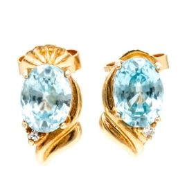 14K Yellow Gold Blue Zircon and Diamond Earrings: A pair of 14K yellow gold blue zircon and diamond earrings. Each earring holds a prong set oval faceted blue zircon and has a single cut diamond set below it amidst two gold flourishes.