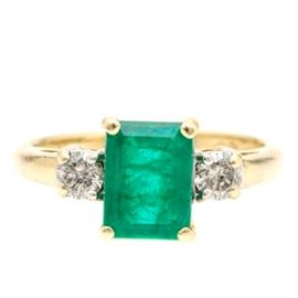 14K Yellow Gold Emerald and Diamond Ring: A 14K yellow gold emerald and diamond ring. This ring features a crown of a prong set emerald step cut emerald that is flanked by two diamonds set in the shoulders.