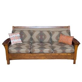 Mission Style Oak Sofa and Ottoman: A Mission style oak sofa and ottoman. The sofa features a wood-framed rectangular backrest, broad, slightly curved wooden armrests, four legs, and parallel slat supports on each shoulder. The front and back of the backrest is covered with repeating southwestern diamond pattern upholstery in light gray, brown, and red. It includes three removable back and seat cushions with matching upholstery, as well as two decorative throw pillows. The ottoman features a square cushion and a matching wooden frame. It is covered in a striped tan, aqua, blue, and red pattern upholstery. The wooden components have a brown finish.