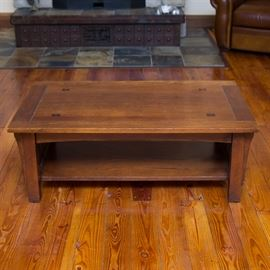 Mission Style Oak Coffee Table: A Mission style oak coffee table. It features a rectangular top with four legs, parallel slat supports on the shoulders, and a bottom shelf. The top is adorned with inset dark wood squares on each corner and routered trim. The piece has a brown finish.