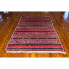 Handmade Central Asian-Inspired Area Rug: A handmade Central Asian-inspired area rug. The rectangular textile features stepped, diamond-shaped patterns positioned on dark red, red, and black parallel stripes adorned with white zigzag thread accents. White fringe caps both ends.