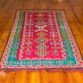Handmade Central Asian-Inspired Area Rug: A handmade Central Asian-inspired area rug. The rectangular textile features orange, blue, green, and white X-shaped and geometric patterns in the center of a red field. This is surmounted by major and minor dark green, white, red, and yellow borders with matching colors. Red fringe caps both ends.