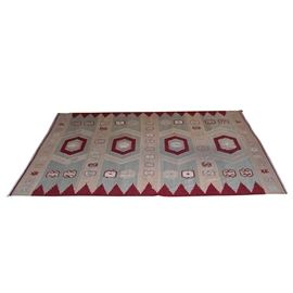 Handmade Central Asian-Inspired Area Rug: A handmade Central Asian-inspired area rug. The rectangular textile features red six-sided medallions set in four respective parallel gray partitions separated by tan stripes. Repeating X-shaped patterns in gray, white, red, and light tan line both ends. Repeating red stepped, triangular trim lines the top and bottom of the rug face.