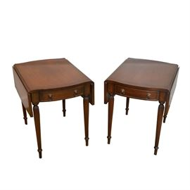 Walnut Dropleaf End Tables: A pair of walnut drop leaf end tables. Each features a slightly scalloped design to the rectangular shaped top with a single bow front drawer finished with cock beading, and a pair of brass lions head bails and round pulls. The top and face of the tables each feature a lined inlay. The tables each rest on four incised tapered legs.