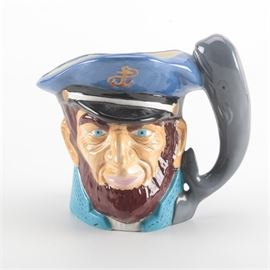 "1981 Toby Style Ceramic Mug of a Sea Captain: A 1981 Toby style ceramic mug of a sea captain. The figural mug features a bearded face wearing a blue cap with a gold tone anchor and a charcoal gray whale handle. Bright blue eyes shine from a tanned, wrinkled face. This piece is marked in the base surface ""For SB From NB – 5/81."