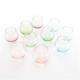 Ten Colored Glass Miniature Snifters: A selection of ten miniature colored glass snifters. These glasses each have a bowl with a base that is slightly wider than the mouth, a short stem, and a round base. The bowls are tinged with pastel colors, including blue, green, red and orange.