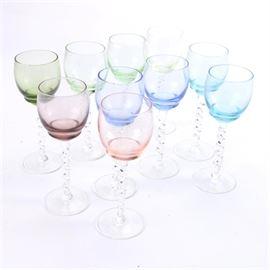 Colored Stemware: A set of colored stemware. This lot of ten wine glasses with translucent bowls features one with dark green, three with light green, two with dark blue bowls, two with light blue, one with purple, and one with a very light purple, almost pink tint to the bowl. All the glassware items have clear roped stems and clear flared feet, and are unmarked.