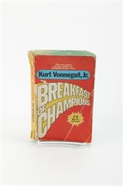 "Circa 1974 Paperback Edition of ""Breakfast of Champions"" by Kurt Vonnegut Jr: A vintage edition of Breakfast of Champions by Kurt Vonnegut Jr. This paperback edition was printed by Dell Publishing Co., Inc. in March of 1974. The first page is marked with a blue tone stamp labeled ""American Book & News Agency, Athens."""