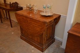 drop-leaf island table with drawer and cabinet on either end