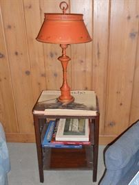 Rust colored tole painted table lamp on small mahogany side table