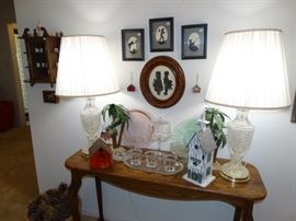 a Nice contemporary Oak sofa table w/ crystal lamps a couple of depression glass platters and candlewick glassware - on the walls more sissor cuttings