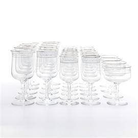 "Lenox ""Moonspun"" Crystal Stemware: A set of Lenox crystal stemware in the Moonspun pattern. Each piece features two silver tone bands with a floral motif pictured between the bands. Included are ten water goblets, four coupe glasses, and twelve wine glasses. Each of the pieces is marked ""Lenox USA"" to the underside."