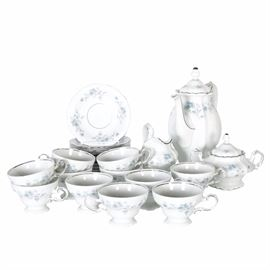 "Johann Haviland Porcelain Tea Set: A Johann Haviland porcelain tea set. This multifaceted set features a total of twenty-five items. Featured items include eleven cups, eleven saucers, one creamer, one sugar bowl and one coffee pot. All items are white with light blue floral painted designs and silver tone accents, marked ""Johann Haviland, Bavaria Germany."""