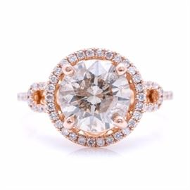 14K Rose Gold 2.97 CTW Diamond Ring: A 14K rose gold 2.97 ctw diamond ring. This ring features a center prong set diamond encircled by a halo of prong set diamonds above a pierced gallery flanked by split diamond set shoulders.