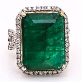 14K White Gold 12.93 CT Emerald and 1.05 CTW Diamond Ring: A 14K white gold 12.93 ct emerald and 1.05 ctw diamond ring. This ring features a yellow gold prong set emerald within a white gold halo of prong set diamonds above a pierced gallery and flanked by diamond encrusted openwork figure eight shoulders.