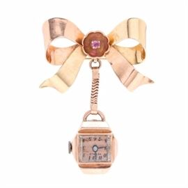 """14K Two Tone Gold Ruby Bow Pin Watch: A 14K two tone gold watch pin featuring a yellow and rose gold ribbon bow motif with central ruby stone accent. The watch case features a domed glass bezel, with black Arabic numeral indexes and two hands against a rose tone dial face signed """"Herald"""". The total weight, inclusive of all materials, is 9.80 dwt."""