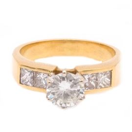 18K Yellow Gold 1.35 CTW Diamond Ring: An 18K yellow gold ring featuring a prong set diamond center stone and two princess cut, channel set diamond side stones to each brightly polished and beveled shoulder. The diamond total carat weight is 1.35 ctw.