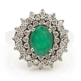 14K White Gold Emerald and Diamond Ring: A 14K white gold emerald and diamond ring. A prong set oval emerald is surrounded by a double halo of round brilliant cut diamonds.