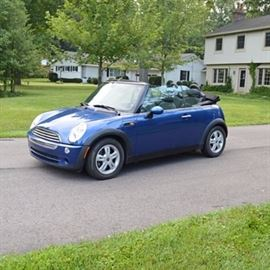 2007 Mini Cooper Convertible: A 2007 Mini Cooper convertible, vin number WMWRF33517TF67230 and mileage of 59,905. This convertible two-door hatchback features a Lightening Blue metallic exterior, black cloth top, and Octogan Panther Black cloth interior. It has a 1.6 liter engine, four-cylinder five-speed manual Getrag transmission, four-wheel anti-lock disc brakes, and Bridgestone EP422 tires. An automatic soft top features a convertible sunroof function and glass rear window. Optional features include a Premium Package with a multi-function steering wheel, a chrome-lined interior, automatic air conditioning, and a Harman-Kardon sound system. It also features an optional Cold Weather Package with heated mirrors and washer jets, and heated front seats.