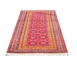 Hand-Knotted Wool Area Rug: A hand-knotted area rug. This wool rug features medallions in a repeating lattice pattern to a red field surrounded by a series of seven unresolved borders. It is hand-crafted in a palette of red, orange, brown, and black with accents of green, slate blue, and cream. It features wool warp fringe to both ends. Unlabeled.