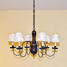 David T. Smith Chandelier: A David T. Smith chandelier. Constructed from wood and black iron, this chandelier features six sockets that extend from curved arms. The sockets are faux candle sticks and sit in crimped bobeches. The paper shades feature a delicate floral design accented with gold gimp braided trim. The turned wood center has a distressed finish with gold trim and extends from a black chain.