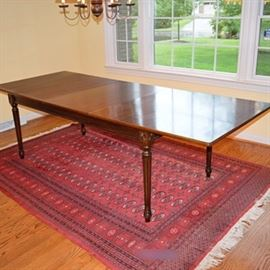 "Extension Dining Table With One Leaf: A four-legged extension table with one leaf. This large table features a rectangular top with eased edges that expands to accommodate one 23.5"" wide leaf. The apron is not split and the legs remain stationary when extended. The wooden slides feature cross supports to house the leaf when not in use. The table is raised on turned fluted legs with floral carvings at the knees. It is constructed of solids and veneers with a walnut finish. Marked as ""Made in Italy""."