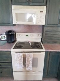 Modern electric range and GE microwave oven.