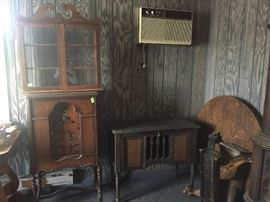 Old radio, record holder (front tilts open) and wall glass door cabinet.