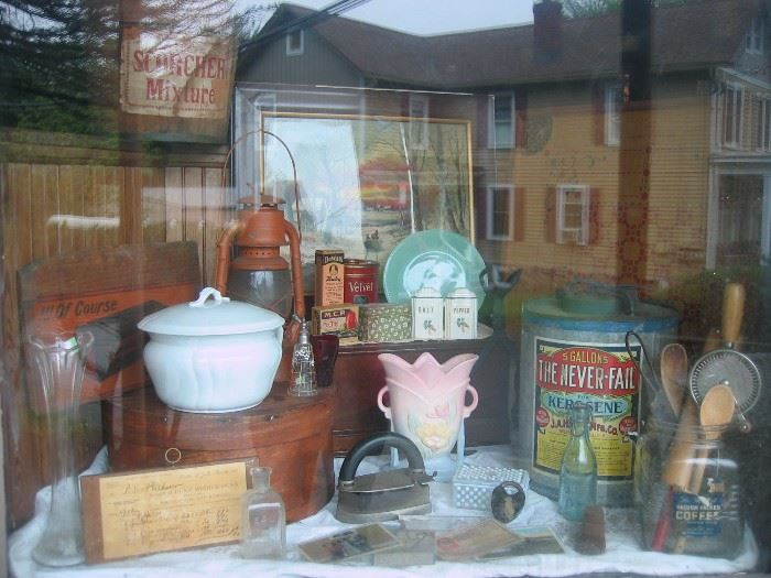 An assortment of items available at sale.  Old tins and boxes with advertising, irons, rolling pins, egg beaters, bottles, vases, chamber pot, railroad lantern, art prints, postcards, etc.