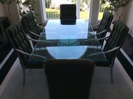 Chrome and glass dining table with six moss green button-tufted chairs.