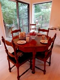 LOVELY ANTIQUE DINING TABLE WITH 4 LEAVES AND SIX NEEDLE POINT CHAIRS.