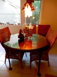 A VERY INTERESTING METAL TABLE WITH A GLASS TOP AND FOUR WICKER CHAIRS